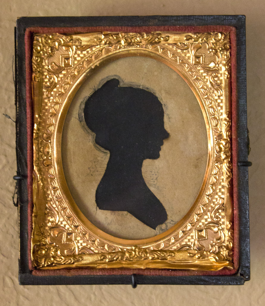 """(above) This is my favorite by far. Tiny, but exquisite. This silhouette is signed """"Wood"""" in ink below the bust with """"Mrs. Sally Worster"""" penciled below that. Since the sitter looks to be in her early twenties, she, most likely, would have been born during the American Revolution. The frame, a one sixteenth plate ambrotype, is not original to the piece. In fact it is the back portion of a hinged box. The cover portion, now detached, has an American flag with 35 stars. Which means that this frame was created some time between 1863 and 1865 during the height of the Civil War when West Virginia became the thirty fifth state. To be more clear, this silhouette predates the frame by many decades. With Russell's custom captures, this little treasure remains unmarred."""